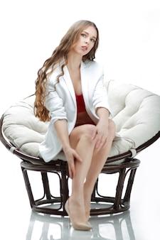 Avvicinamento. ritratto di giovane donna sexy in biancheria che si siede nella sedia papasan.