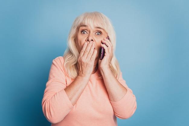 Ritratto ravvicinato di una donna matura pazza scioccata che parla sullo smartphone