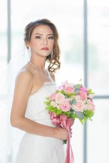 Primo piano ritratto di bella sposa asiatica in piedi e con in mano un mazzo di fiori nello spogliatoio.