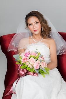 Close up ritratto di sorriso bella sposa asiatica seduta su una sedia rossa con in mano un mazzo di fiori su sfondo grigio.