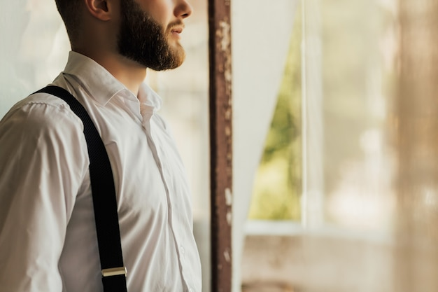 Chiuda sul ritratto della vista laterale dell'uomo di modo bello cura vicino alla finestra in interni dal design classico.