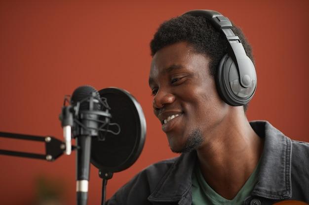Close up ritratto di sorridere afro-americano uomo che canta al microfono su sfondo rosso in studio di registrazione, copia spazio