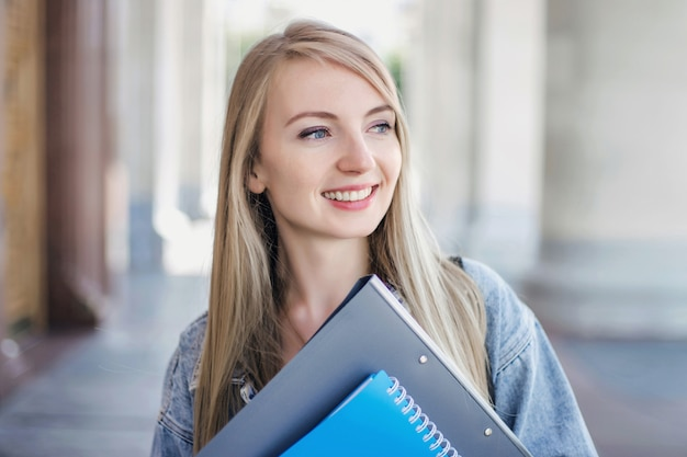 Chiuda sul ritratto di una bionda studentessa sorridente ragazza caucasica con gli occhi azzurri in piedi sullo sfondo di un'antica università e tenendo cartelle e quaderni