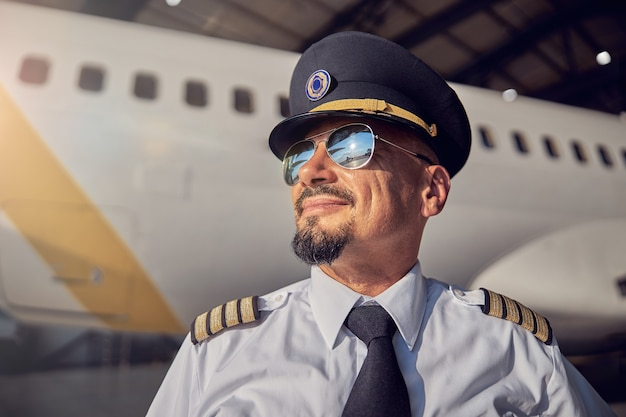 Ritratto ravvicinato di un uomo sorridente fiducioso in camicia bianca e cravatta scura in piedi di fronte all'aereo passeggeri