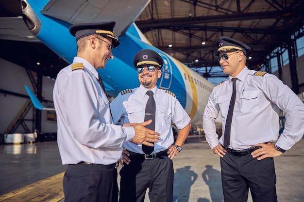 Ritratto ravvicinato di bei piloti sorridenti in tailleur e occhiali da sole che parlano insieme mentre trascorrono del tempo nell'hangar dell'aviazione vicino all'aereo passeggeri