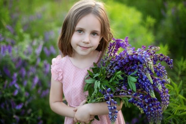 Close up ritratto di una bambina sorridente in abito rosa e con un grande mazzo di lupini.