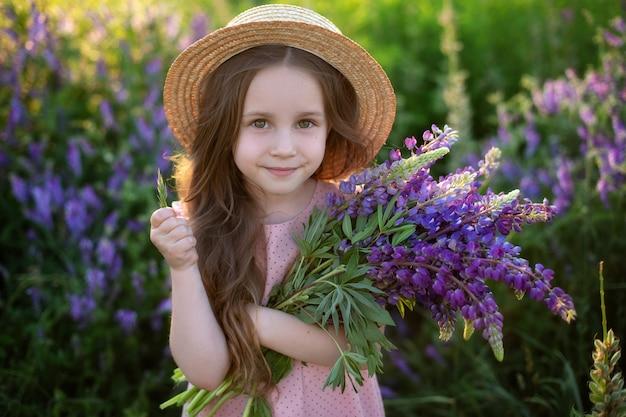 Chiuda sul ritratto di una bambina sorridente in un cappello di paglia e con un grande mazzo di lupini