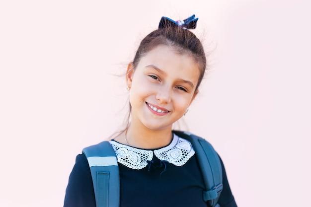 Ritratto del primo piano di una ragazza sorridente della scuola isolata sulla parete rosa-chiaro.