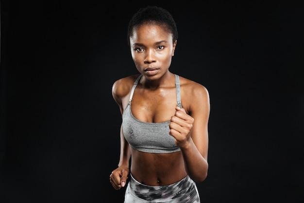 Ritratto del primo piano di una donna sportiva che corre isolata su un muro nero black