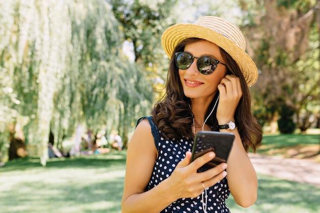 Close up ritratto di donna di stile sta camminando nel parco estivo indossando cappello estivo e occhiali da sole neri e vestito carino. sta ascoltando musica.