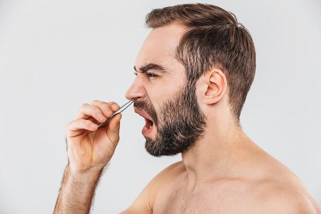 Close up ritratto di una sofferenza uomo barbuto in piedi isolato su bianco, strappandosi i peli del naso