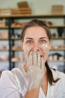 Ritratto ravvicinato di una ceramista artigiana sorpresa che si copre la bocca con le mani spalmate di argilla grigia