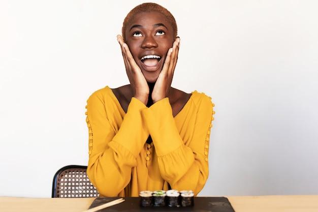Close up ritratto di giovane donna afroamericana sorpresa guardando verso l'alto con le mani a coppa intorno alla bocca