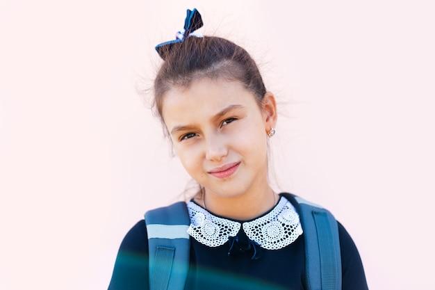 Ritratto del primo piano dell'adolescente, sullo sfondo del muro rosa pastello.
