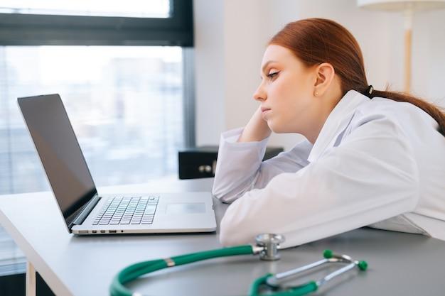 Ritratto ravvicinato di una giovane dottoressa stanca esausta in camice bianco seduta alla scrivania con laptop e guardando lo schermo.