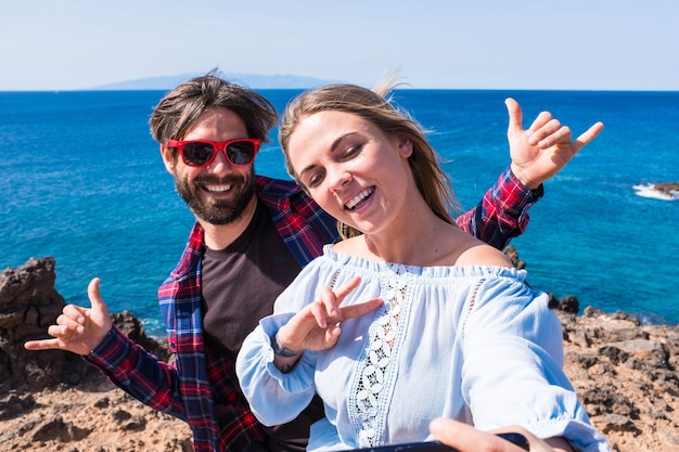 Primo piano e ritratto di due persone belle e felici che scattano una foto selfie insieme in spiaggia con un'isola e il mare sullo sfondo - foto divertente e felice delle vacanze e dei viaggi dell'erede