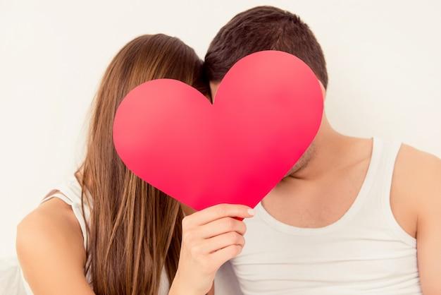 Close up ritratto di due amanti che nascondono i volti dietro il grande cuore di carta