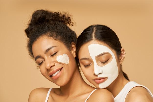Primo piano ritratto di due giovani amiche con maschere facciali.