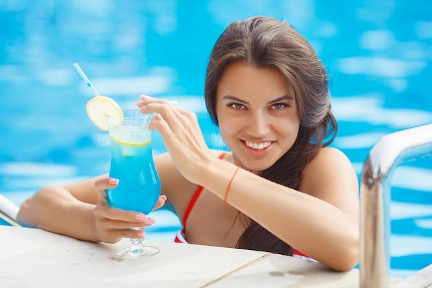 Chiuda sul ritratto di una giovane donna molto bella nella piscina