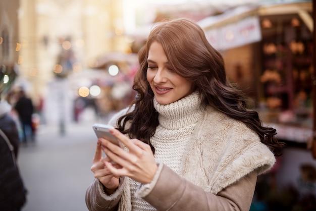 Close up vista verticale di carino elegante attraente bella giovane ragazza felice in maglione e giacca in possesso di un cellulare e in piedi in città fulmini strada.