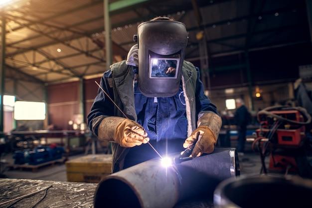 Chiuda sulla vista verticale dell'uomo saldatore protetto maschera professionale in uniforme lavorando sulla scultura in metallo al tavolo nel laboratorio di tessuto industriale davanti a pochi altri lavoratori.