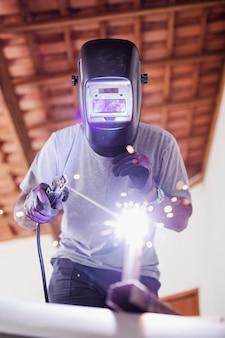 Primo piano verticale di un saldatore di maschere professionale protetto che lavora su una scultura in metallo