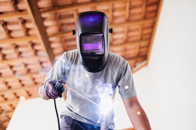 Primo piano verticale di un saldatore di maschere professionale protetto che lavora