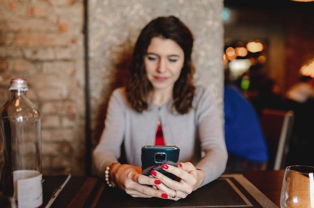 Ritratto del primo piano con la giovane donna caucasica che utilizza smartphone. messaggio di testo, concetto di tecnologia.