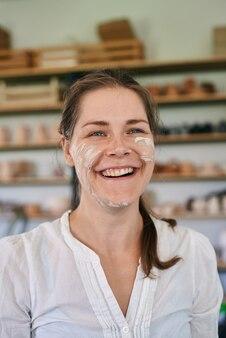 Close-up ritratto di donna artigiana ceramista spalmato in argilla grigia face