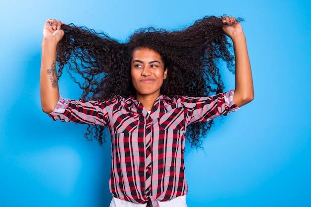 Chiuda sul ritratto di giovane donna africana che tira i capelli ricci cattivi e che sembra preoccupato.
