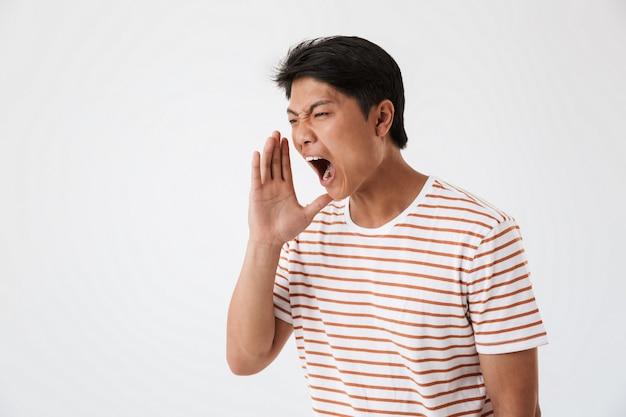Close up ritratto di un giovane uomo asiatico che grida ad alta voce