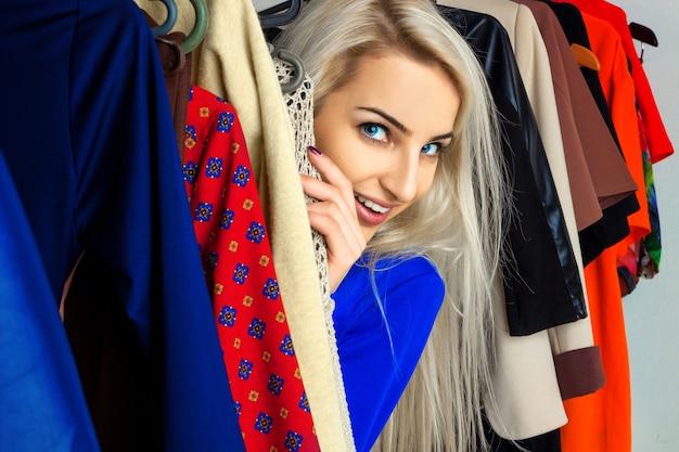 Chiuda sul ritratto di giovane bella bionda nel negozio di abbigliamento
