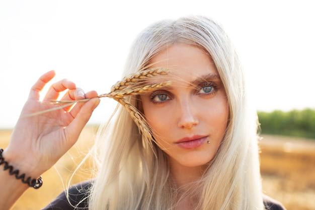 Ritratto del primo piano di giovane bella ragazza bionda che tiene alcuni picchi di grano.