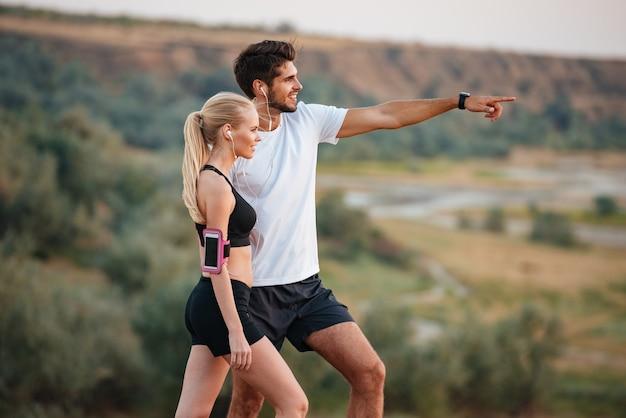 Close up ritratto di una giovane coppia bella fitness in piedi su una collina e guardando qualcosa