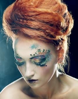 Ritratto del primo piano di giovane bella donna con trucco luminoso variopinto
