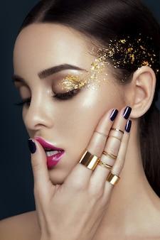 Ritratto di una giovane ragazza bruna da vicino che tiene il dito sulle labbra in modo sensuale
