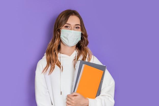 Primo piano ritratto di giovane studentessa bruna con maschera medica chirurgica che indossa una felpa con cappuccio bianca in piedi e guardando la telecamera isolata su sfondo lilla