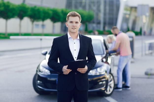 Ritratto del primo piano di un giovane rivenditore di auto in giacca e cravatta. dietro di lui, una giovane coppia, un uomo e una donna ispezionano un'auto nuova. acquisto di macchine, giro di prova.