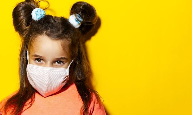 Ritratto del primo piano della ragazza dei bambini piccoli che indossa la mascherina medica contro i virus