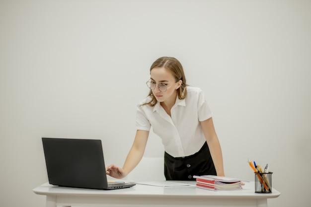 Ritratto del primo piano di un giovane responsabile dell'ufficio femminile sicuro al suo posto di lavoro, pronto per fare attività di affari.