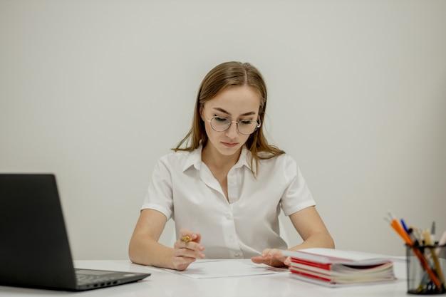 Ritratto del primo piano di un giovane responsabile dell'ufficio femminile sicuro al suo posto di lavoro, pronto per fare attività di affari