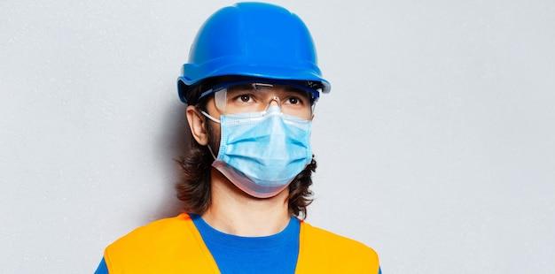 Ritratto ravvicinato di giovane uomo sicuro di sé con maschera medica sul viso, ingegnere operaio edile che indossa attrezzature di sicurezza su sfondo grigio strutturato. prevenzione covid-19.