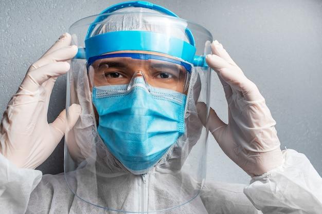 Ritratto del primo piano di un giovane medico che indossa la tuta dpi contro il coronavirus e il covid-19.