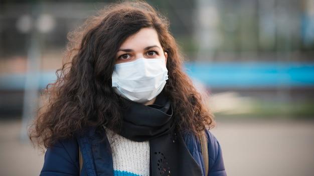 Close-up ritratto giovane donna europea in protettiva monouso medico maschera per il viso camminare all'aperto. nuovo coronavirus (covid-19). concetto di assistenza sanitaria durante un'epidemia o una pandemia