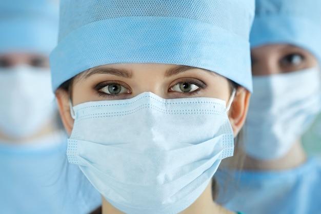 Close up ritratto di giovane donna medico chirurgo circondato dalla sua squadra