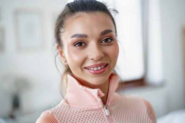 Ritratto ravvicinato di una giovane ragazza in forma in tuta sportiva arancione
