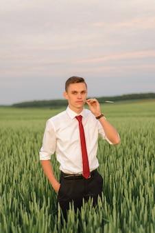 Ritratto di close-up di un giovane sposo. un uomo sgranocchia una cannuccia in un campo di grano.
