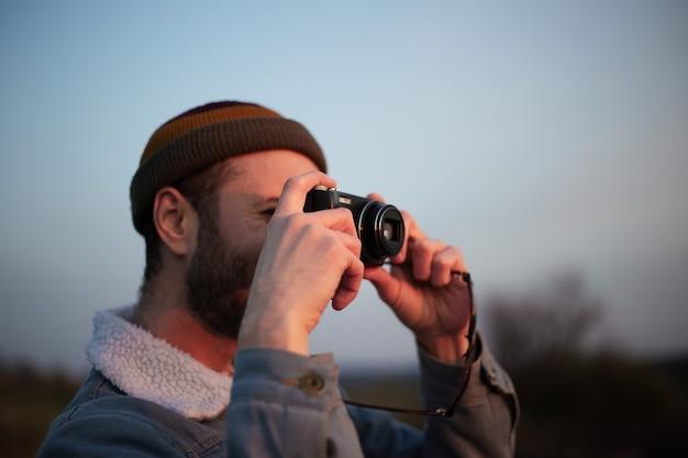 Chiuda sul ritratto di giovane ragazzo che cattura foto dalla fotocamera digitale