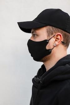 Ritratto ravvicinato di un giovane ragazzo con una maschera medica protettiva e un berretto finto nero elegante in una felpa con cappuccio alla moda su uno sfondo grigio, vista laterale