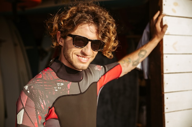 Chiuda sul ritratto di un giovane uomo riccio bello in costume da bagno e occhiali in piedi presso la capanna di surf in spiaggia